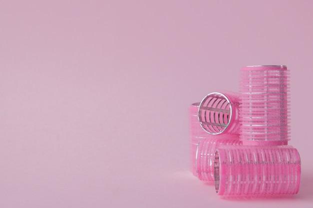 Bigodini di plastica per capelli su uno spazio rosa con copia spazio