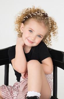 Bambina riccia sorridente su bianco