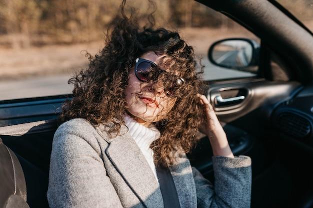 La bella donna riccia in un'auto decappottabile in una giornata di sole con gli occhiali da sole si rilassa e si sente libera
