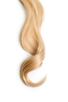 Capelli biondi ricci isolati su sfondo bianco. bella ciocca di capelli biondi lunghi sani, taglio di capelli, acconciatura. capelli tinti o colorazione, estensione dei capelli, cura, concetto di trattamento.
