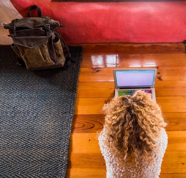 Donna bionda riccia che lavora al computer portatile sul pavimento in camera d'albergo o casa vista dall'alto