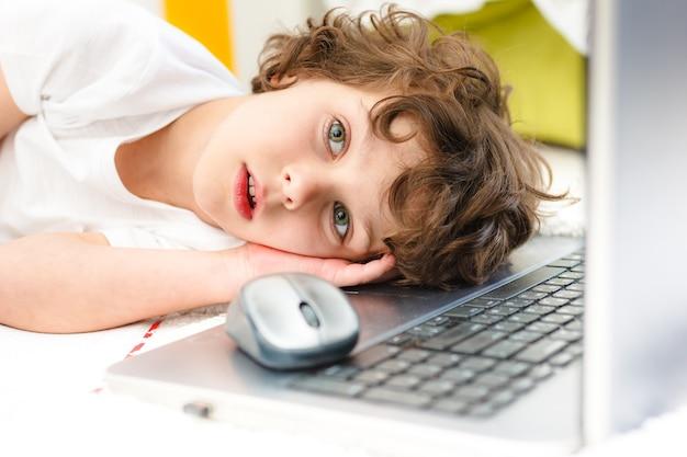 Il ragazzo riccio è impegnato al computer. bambino stanco si trova coprendosi il viso con le mani concetto di difficoltà di scolarizzazione domestica, studio a distanza
