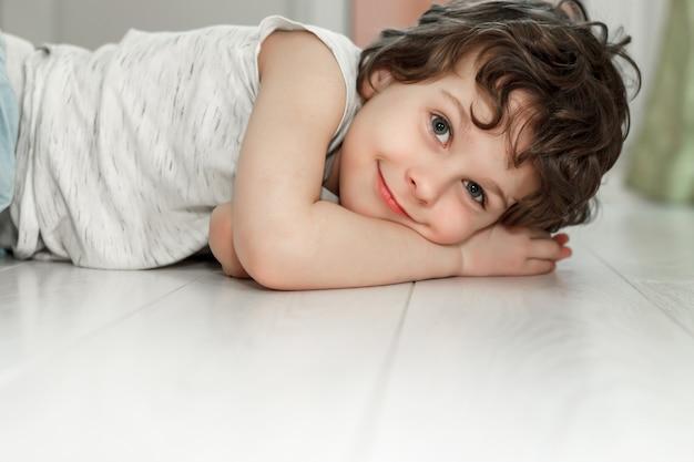 Ragazzo riccio sdraiato sul pavimento bianco a casa e sorridente. il concetto di riscaldamento a pavimento, laminato di qualità.