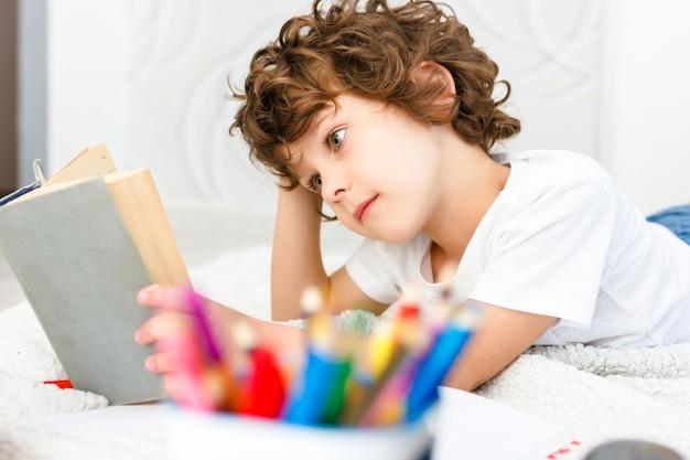 Il ragazzo riccio legge un libro spesso