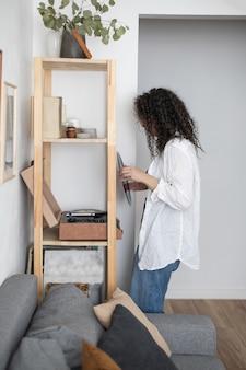 L'amante della musica della donna bruna riccia accende il disco in vinile sul grammofono del lettore musicale vintage del giradischi