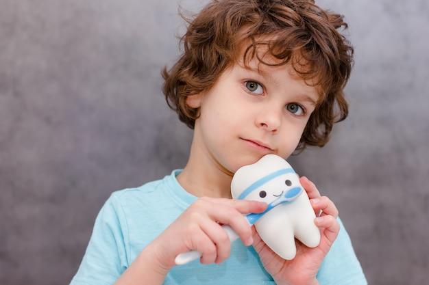 Il ragazzo riccio del bambino pulisce i denti del giocattolo grande sul muro grigio. concetto di igiene orale.