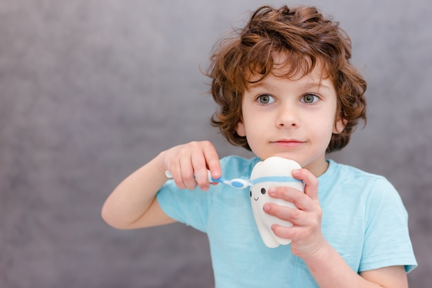 Il ragazzo riccio del bambino pulisce i denti grandi del giocattolo su gray