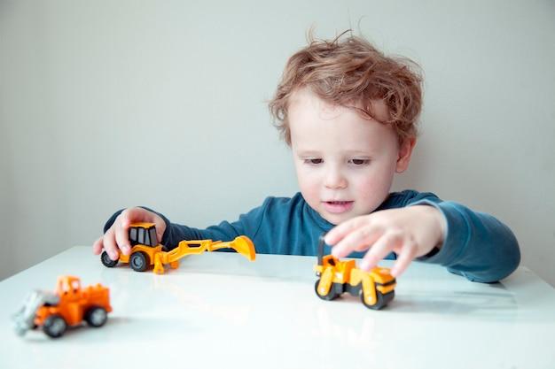 Il ragazzino sveglio riccio che gioca con i cubi di plastica e le automobili si è seduto al tavolo.