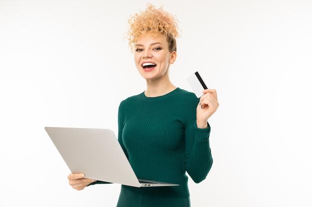 Ragazza riccia che tiene un computer portatile in sue mani sulla parete bianca