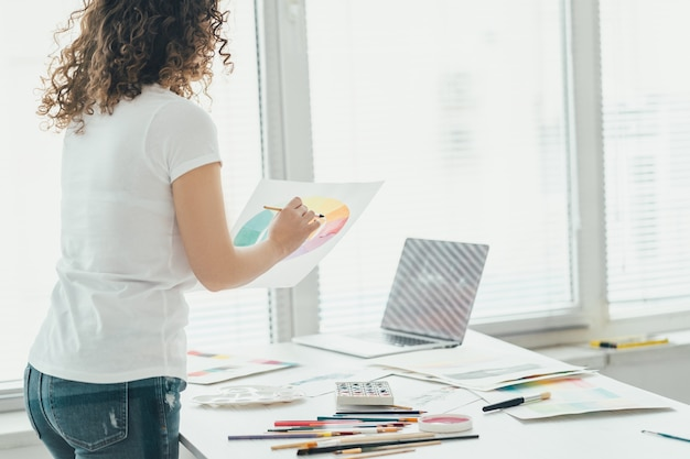 La ragazza riccia con un pennello che fa un disegno a tavola