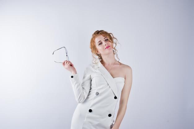 Ragazza dei capelli ricci in vetri isolati sullo studio bianco
