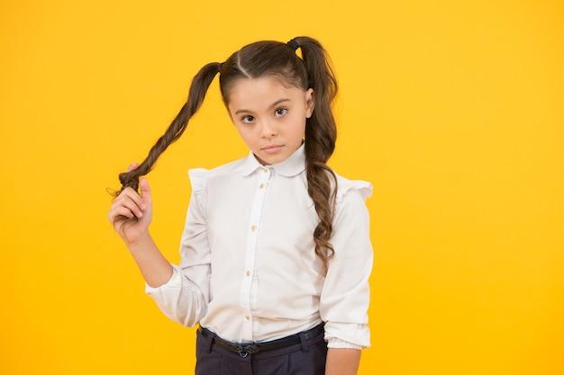 Coda di cavallo riccia per il ritorno a scuola. adorabile piccola ragazza che torce i capelli intorno al dito su sfondo giallo. piccolo bambino sveglio con capelli lunghi del brunette. acconciatura per la scuola.