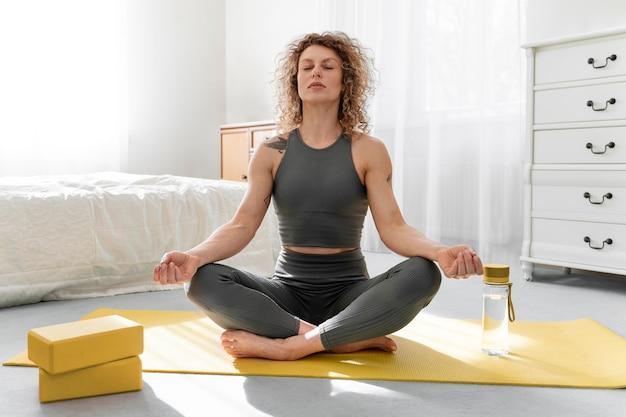 Donna bionda dai capelli ricci che fa yoga a casa