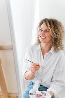 Donna bionda dai capelli ricci che dipinge a casa