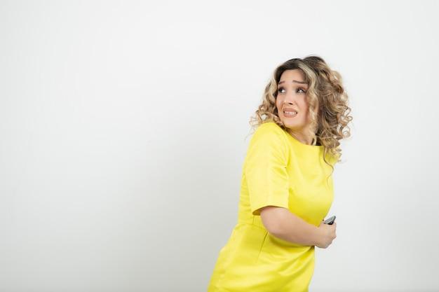 Donna bionda dai capelli ricci in abito giallo che nasconde il suo cellulare.