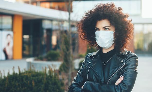 La donna di affari dai capelli ricci indossa una maschera medica e posa con le mani incrociate all'esterno