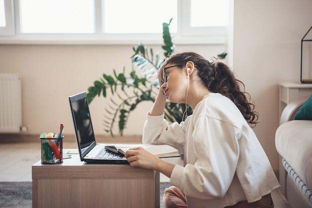 Donna caucasica dai capelli riccia stanca delle lezioni che indossano occhiali e cuffie facendo i compiti al computer portatile