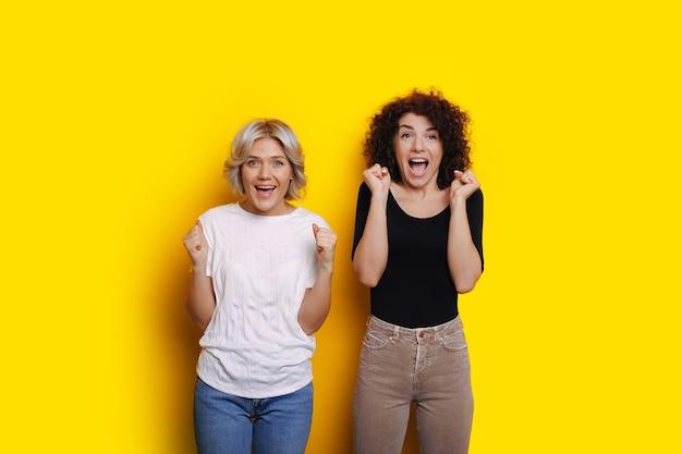 La ragazza dai capelli ricci e la sorella bionda sono sorprese da qualcosa che gesticola su uno sfondo giallo