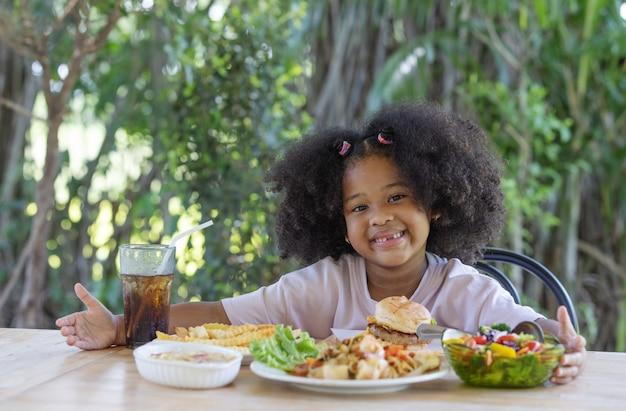 La ragazza dai capelli ricci ha goduto di una varietà di piatti sul tavolo