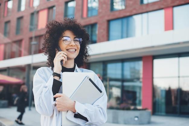 Signora dai capelli ricci che ha una discussione telefonica durante una passeggiata mentre tiene i suoi gadget