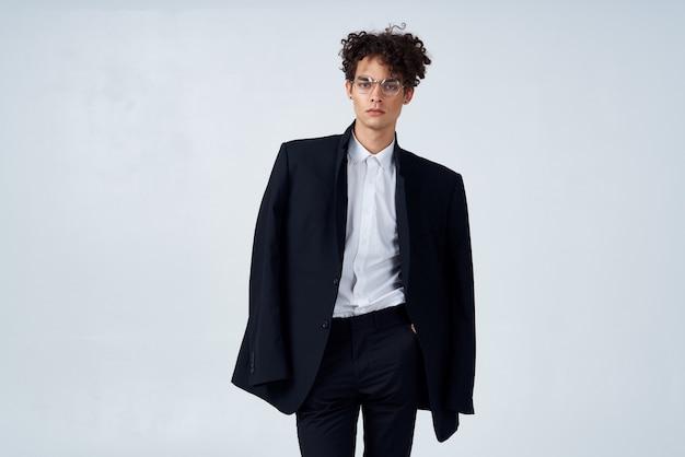 Uomo dai capelli ricci in abito nero in studio