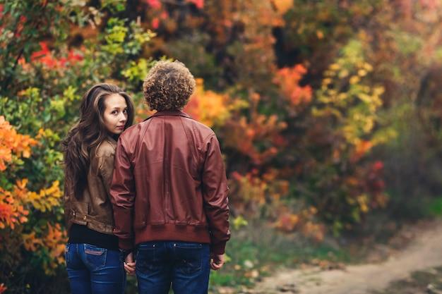 L'uomo dai capelli ricci ha voltato le spalle e la ragazza fa capolino da dietro la sua spalla. coppia di innamorati su bellissimi alberi autunnali colorati.