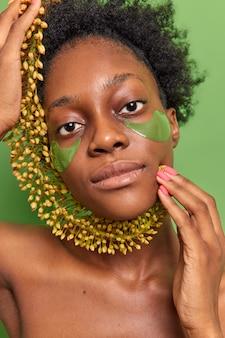 La donna seria dai capelli ricci con applica cerotti per idratare tiene la pianta selvatica vicino al viso guarda seriamente la telecamera si trova in topless isolato sul muro verde. concetto di giorno di bellezza