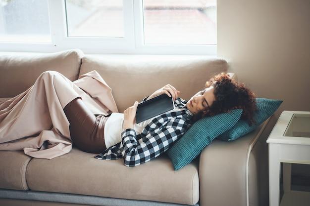 Studente dai capelli ricci dorme nel letto coperto da un copriletto dopo aver letto un libro