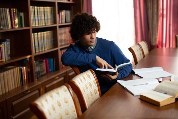 Lo studente dai capelli ricci è seduto circondato da libri aperti e in biblioteca