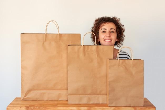 Una donna dai capelli ricci dietro alcune borse della spesa con sfondo bianco isolato