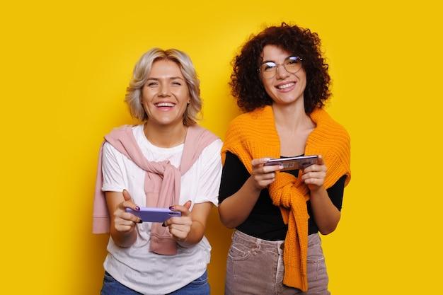 La donna dai capelli ricci con gli occhiali è in posa nella sua sorella bionda mentre gioca ad alcuni giochi per cellulare