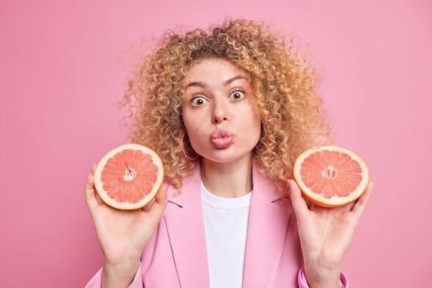 La giovane donna dai capelli ricci tiene le labbra piegate ha un'espressione romantica tiene due fette di pompelmo fresco e succoso mantiene le diete per fare il succo essendo vegetariano per fare un prodotto cosmetico