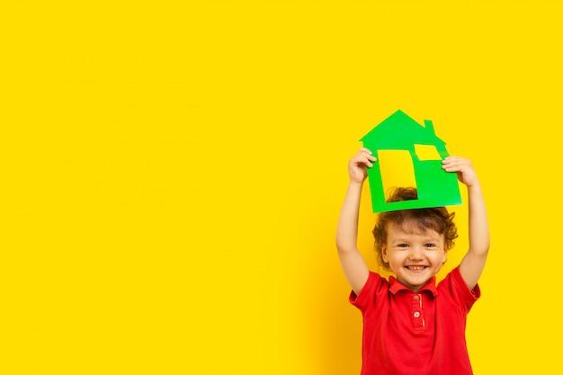 Un bambino emotivo che ride riccio tiene una casa di cartone di colore verde sopra la sua testa