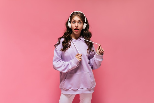 Donna riccia dai capelli lunghi in felpa con cappuccio viola e pantaloni bianchi che ascolta musica in cuffia
