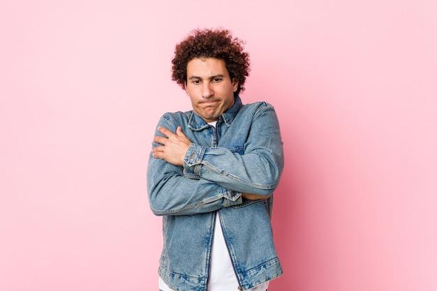 Uomo maturo riccio che indossa una giacca dinim contro il rosa che diventa freddo a causa della bassa temperatura o di una malattia.