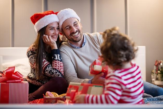 Ragazza riccia del piccolo bambino che guarda nei genitori mentre loro si siedono felici ed elettrizzati sul letto con i regali per le vacanze di natale.