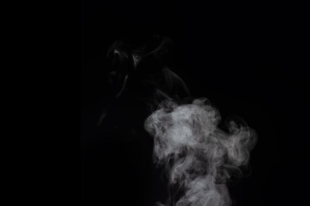 Vapore bianco riccio che sale e spruzzi d'acqua che si disperdono in direzioni diverse isolate su uno sfondo nero.