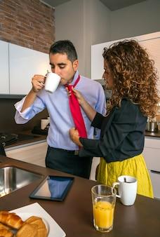 Donna riccia che regola la cravatta di un uomo d'affari stressato mentre fa colazione veloce prima di andare al lavoro
