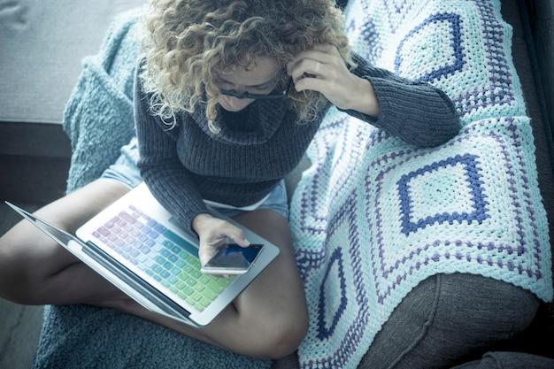 Donna riccia e occhiali passa il tempo a chiacchierare con il telefono seduto sul divano nel comfort di casa sua tecnologia e dispositivo portatile ufficio alternativo e postazione di lavoro per una bellezza indipendente