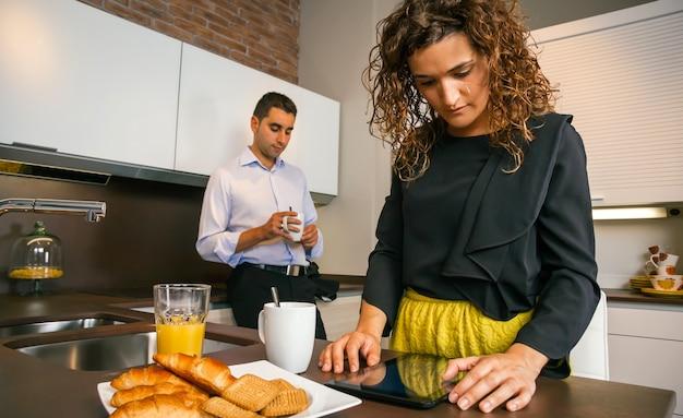 Donna riccia che guarda un tablet elettronico mentre il giovane prende un caffè veloce a casa prima di andare al lavoro
