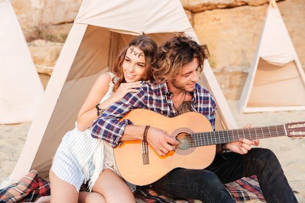 Giovane riccio che suona la chitarra per la sua ragazza seduta alla tenda da campeggio