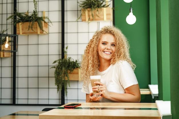 Giovane donna riccia che si siede al tavolo in caffetteria e rilassante con una tazza di caffè, ritratto