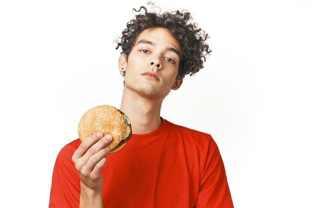 Fast food ragazzo dai capelli ricci nelle mani di uno spuntino dieta sfondo chiaro