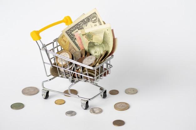 Valuta di diversi paesi. un carrello pieno di soldi, dollari di carta, grivna, yuan e monete varie. cambio di valuta. cambio di denaro. soldi diversi.