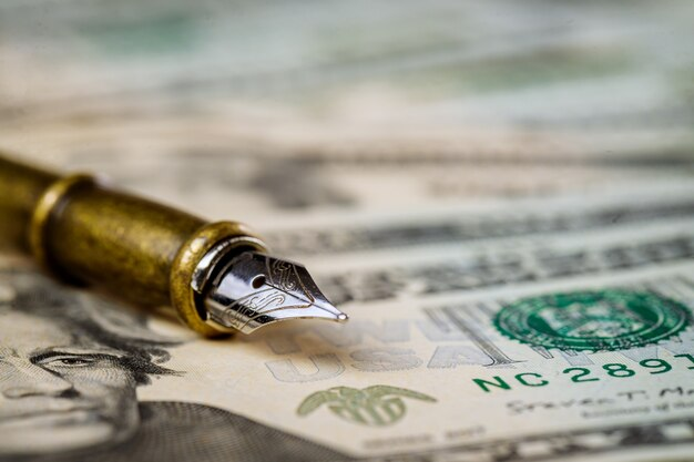 Valuta il primo piano delle banconote del dollaro americano con la penna a sfera sulle banconote dei dollari