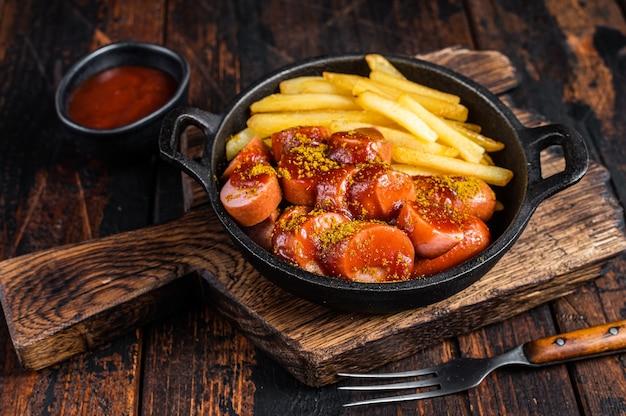 Salsicce al currywurst con spezie al curry su wurstel servite patatine fritte in padella. tavolo in legno scuro. vista dall'alto.