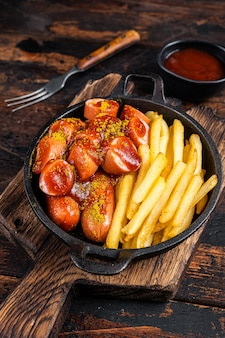 Salsicce al curry con spezie al curry su wurstel servite in padella con patatine fritte