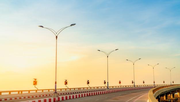Strada in cemento curva con segnale stradale di curva e sentiero accanto al mare all'ora del tramonto. energia del pannello solare sul segnale stradale giallo della curva. viaggio in macchina durante le vacanze estive. segnale stradale rosso e bianco.