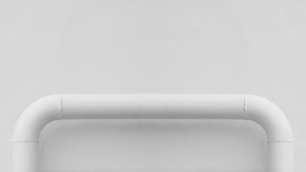 Curva del tubo di acciaio bianco al muro di cemento bianco.