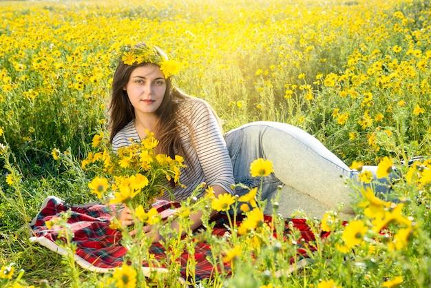 Una modella sinuosa che giace in un campo di margherite. sguardo sensuale e corona di fiori